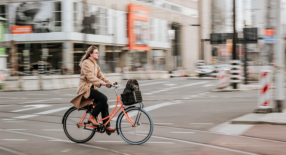 A woman rides an orange bike in Rotterdam, Netherlands
